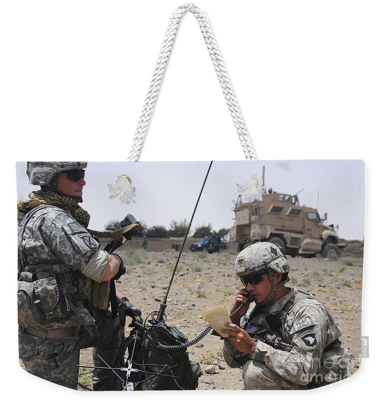 Portable Weekender Tote Bag featuring the photograph Soldiers Setting Up A Satellite by Stocktrek Images