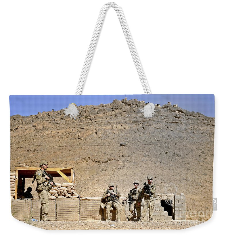 Provincial Reconstruction Team Weekender Tote Bag featuring the photograph Soldiers Wait For Afghan National by Stocktrek Images
