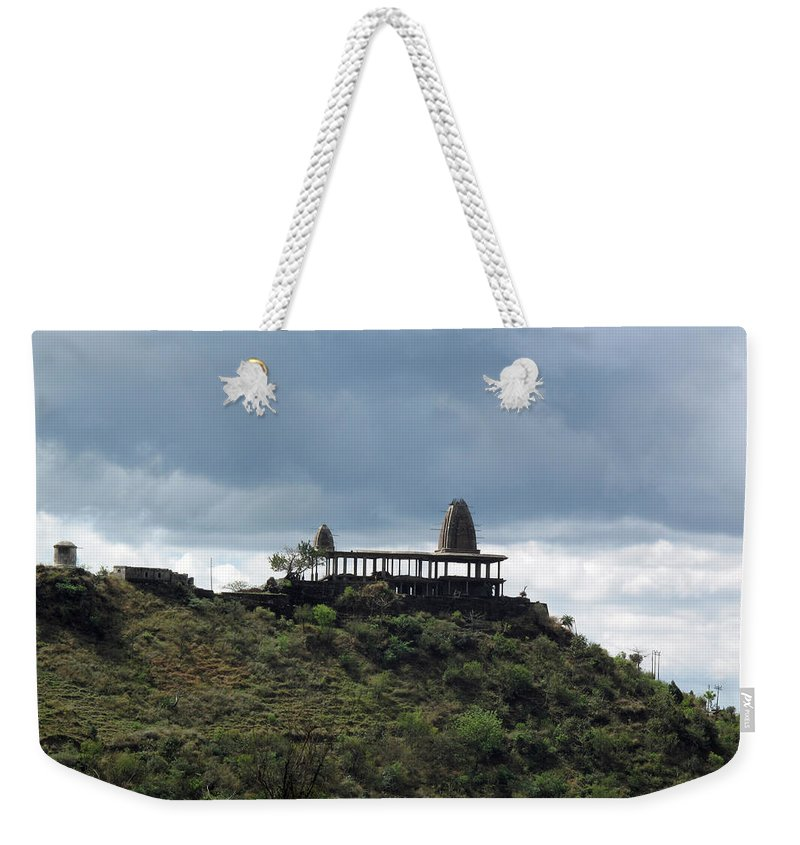 Jammu Weekender Tote Bag featuring the photograph The Structure Of An Abandoned Temple On The Top Of A Green Covered Hill With Blue And White Clouds I by Ashish Agarwal