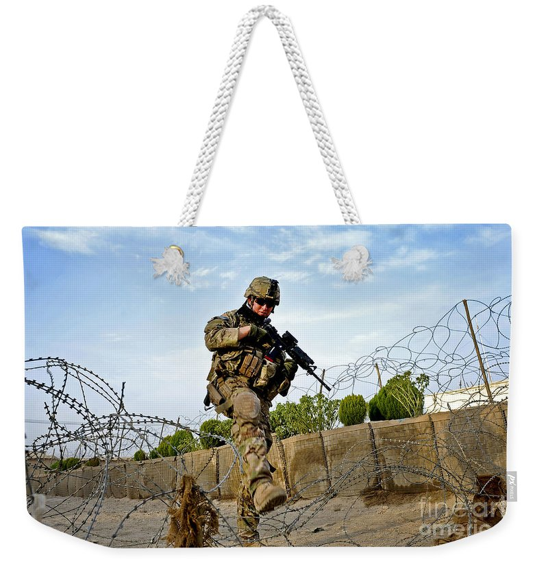 Provincial Reconstruction Team Weekender Tote Bag featuring the photograph U.s. Air Force Airman Patrols by Stocktrek Images