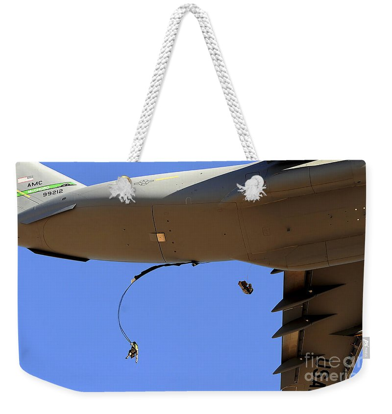 C-17 Weekender Tote Bag featuring the photograph U.s Air Force Airmen Parachute by Stocktrek Images
