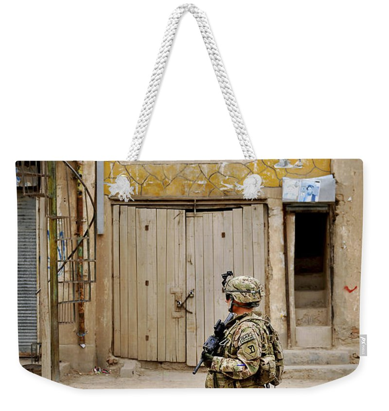Provincial Reconstruction Team Weekender Tote Bag featuring the photograph U.s. Air Force Senior Airman Patrols by Stocktrek Images