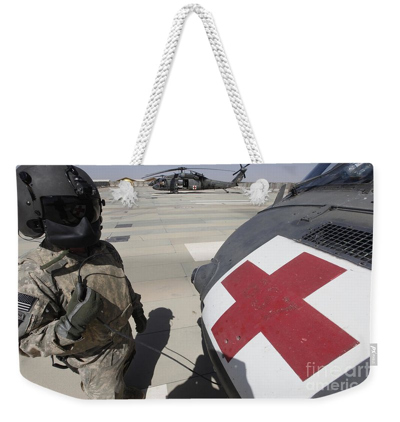 Uh-60 Blackhawk Weekender Tote Bag featuring the photograph U.s. Army Crew Chief Inspects by Stocktrek Images