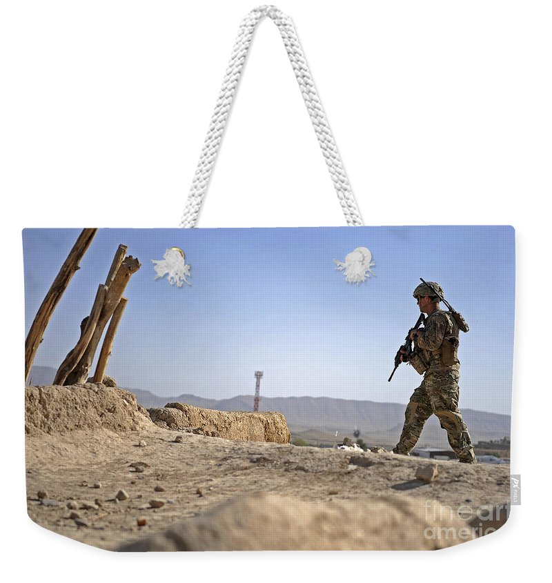 Provincial Reconstruction Team Weekender Tote Bag featuring the photograph U.s. Army Soldier On A Foot Patrol by Stocktrek Images
