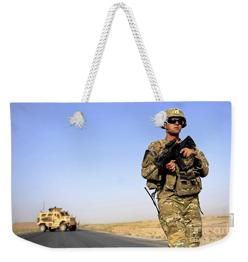 Provincial Reconstruction Team Weekender Tote Bag featuring the photograph U.s. Army Soldier On Patrol by Stocktrek Images