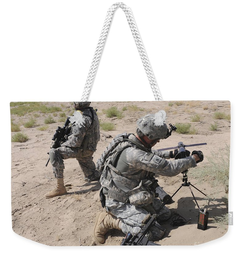 Iraq Weekender Tote Bag featuring the photograph U.s. Army Soldier Sets Up A Satellite by Stocktrek Images