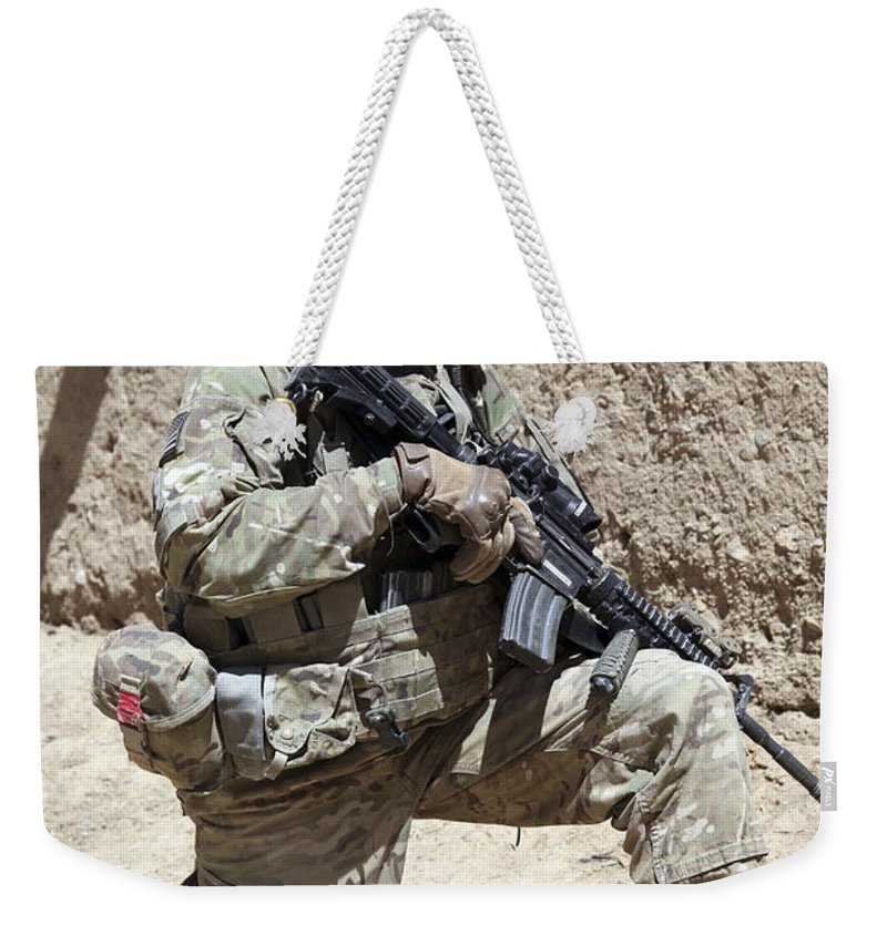 Afghanistan Weekender Tote Bag featuring the photograph U.s. Army Soldier Takes A Knee While by Stocktrek Images