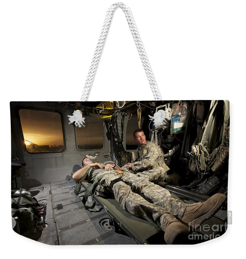 Us Army Weekender Tote Bag featuring the photograph U.s. Army Specialist Practices Giving by Terry Moore