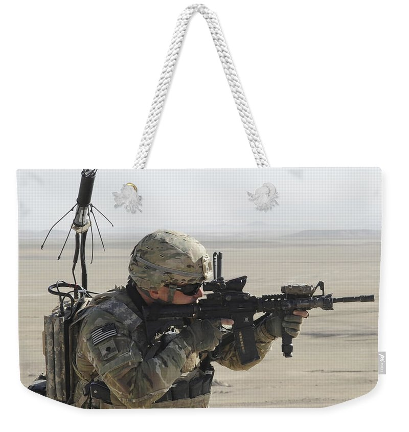 Provincial Reconstruction Team Weekender Tote Bag featuring the photograph U.s. Army Specialist Scans His Area by Stocktrek Images