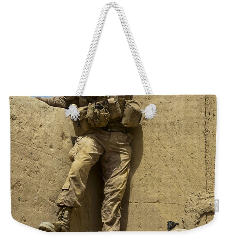 Afghanistan Weekender Tote Bag featuring the photograph U.s. Marine Climbs Down From An by Stocktrek Images