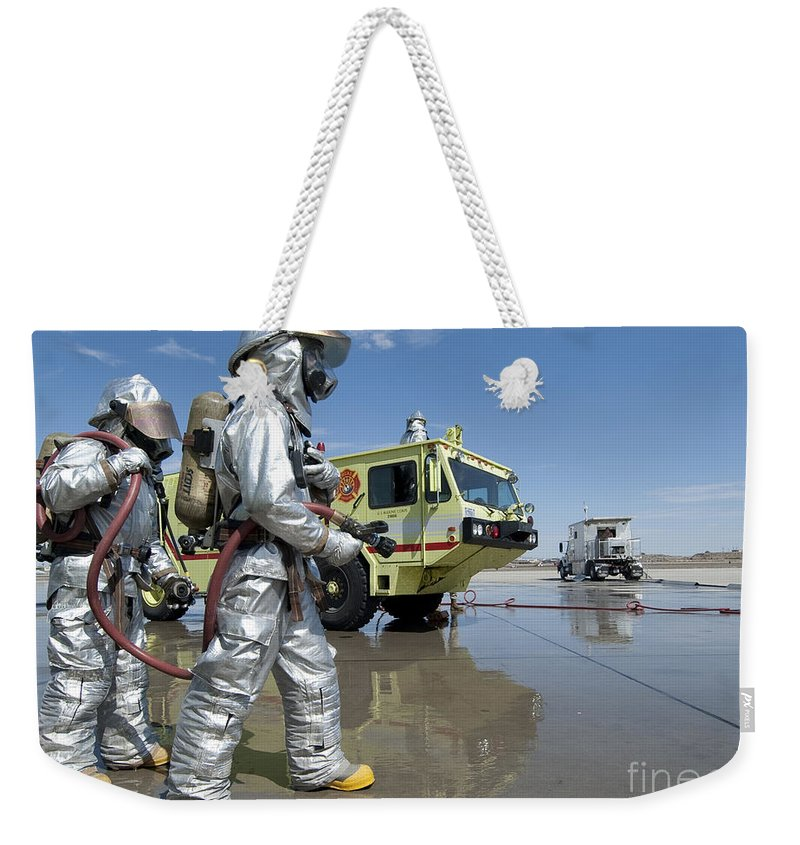 Protective Clothing Weekender Tote Bag featuring the photograph U.s. Marine Firefighters Stand Ready by Stocktrek Images