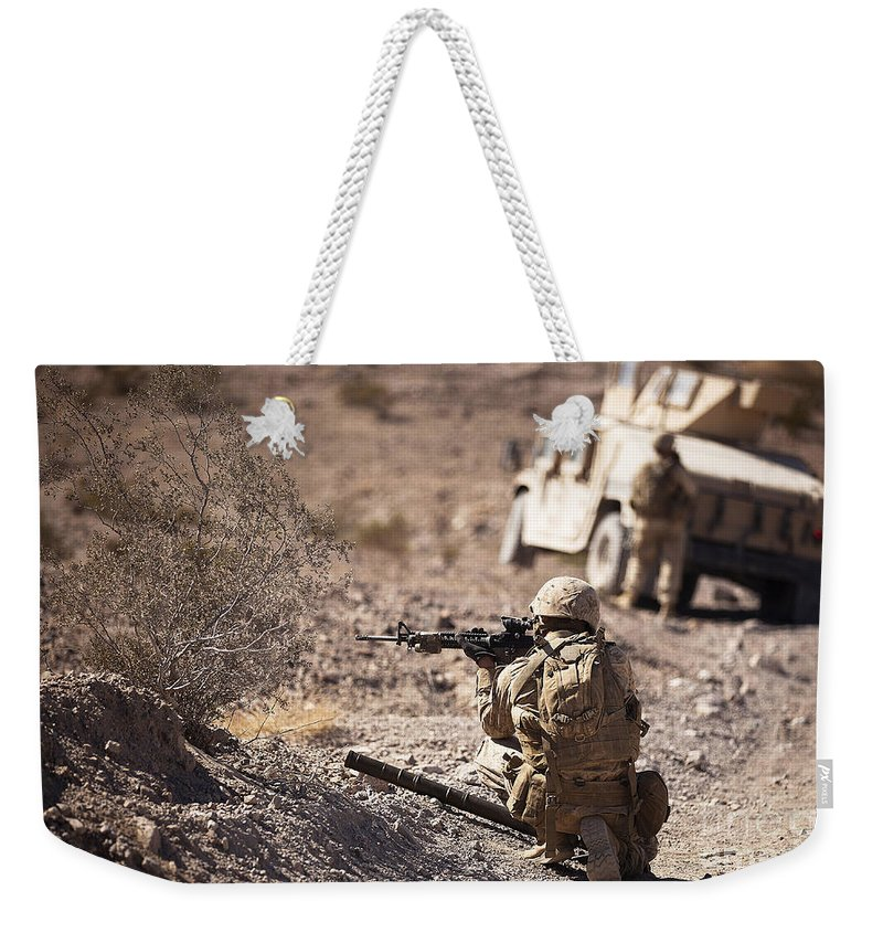 Looking Weekender Tote Bag featuring the photograph U.s. Marine Scans His Area While by Stocktrek Images