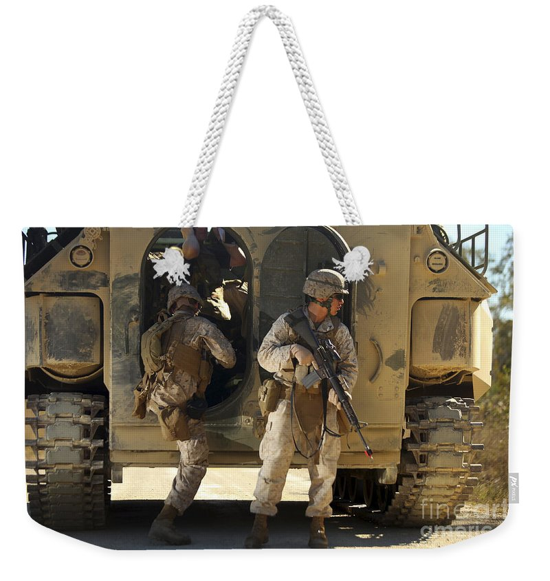Battalion Weekender Tote Bag featuring the photograph U.s. Marines Climb Into The Back Of An by Stocktrek Images