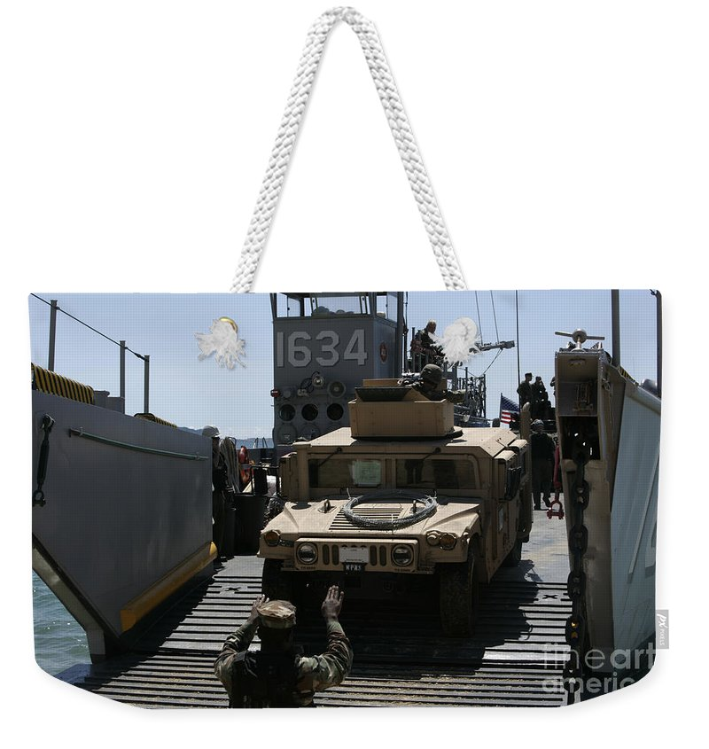 Marine Expeditionary Unit Weekender Tote Bag featuring the photograph U.s. Marines Load An M1114 Humvee Onto by Stocktrek Images