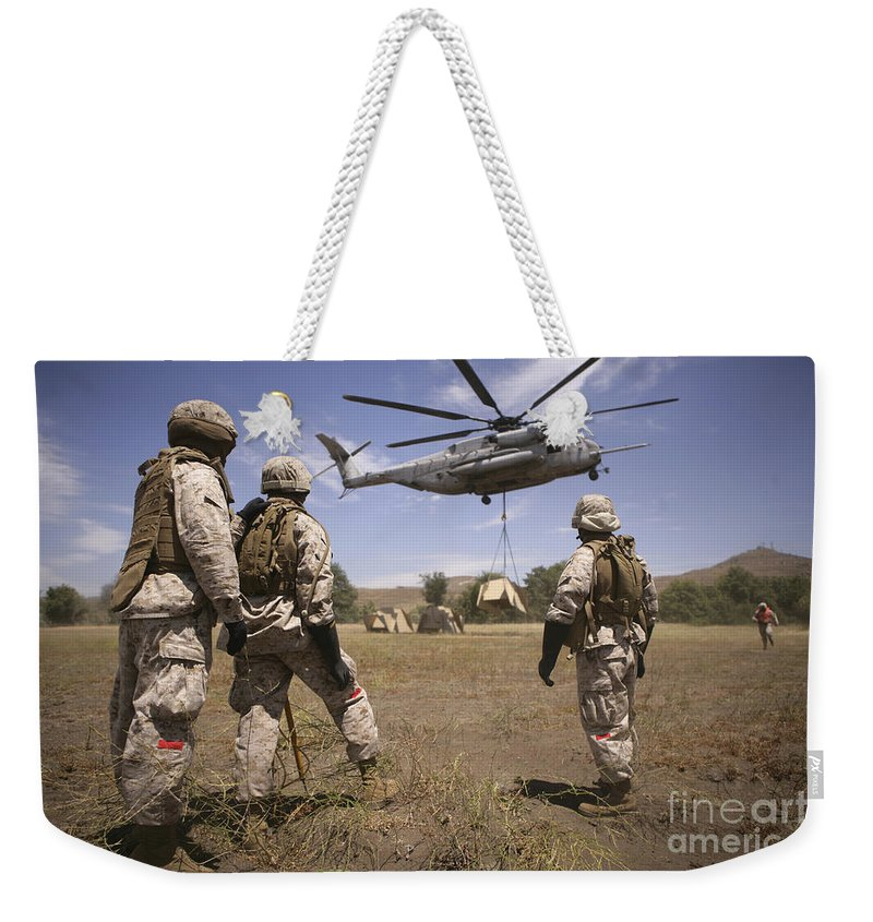 Extraction Weekender Tote Bag featuring the photograph U.s. Marines Observe Ch-53e Super by Stocktrek Images