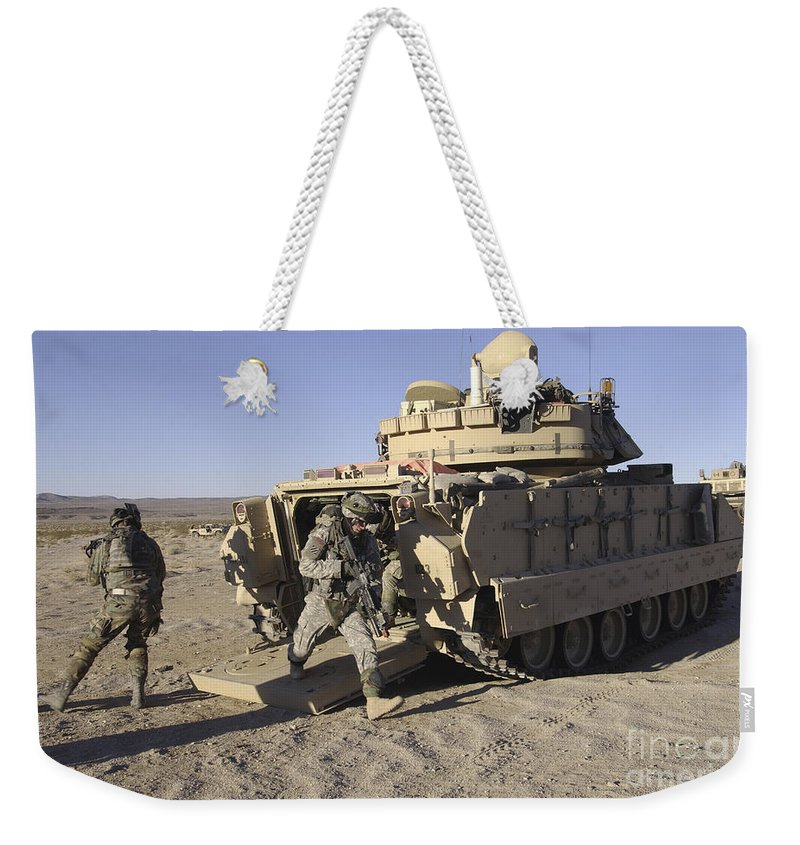 Army Weekender Tote Bag featuring the photograph U.s. Soldiers Exit From An M2 Bradley by Stocktrek Images