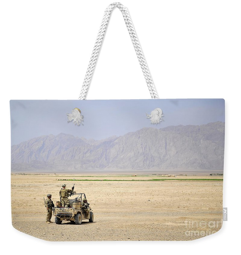 Military Weekender Tote Bag featuring the photograph U.s. Soldiers Provide Security by Stocktrek Images