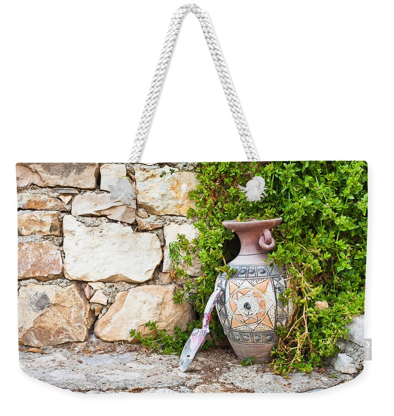 Background Weekender Tote Bag featuring the photograph Vase And Trowel by Tom Gowanlock