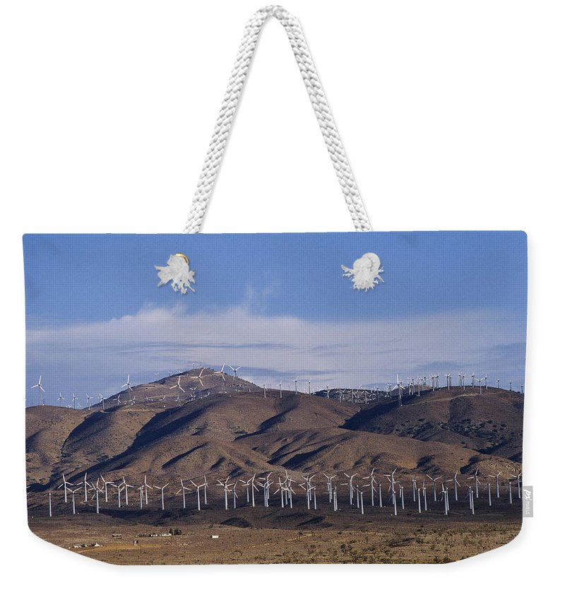 North America Weekender Tote Bag featuring the photograph View Of Windmill Structures On A Wind by Marc Moritsch