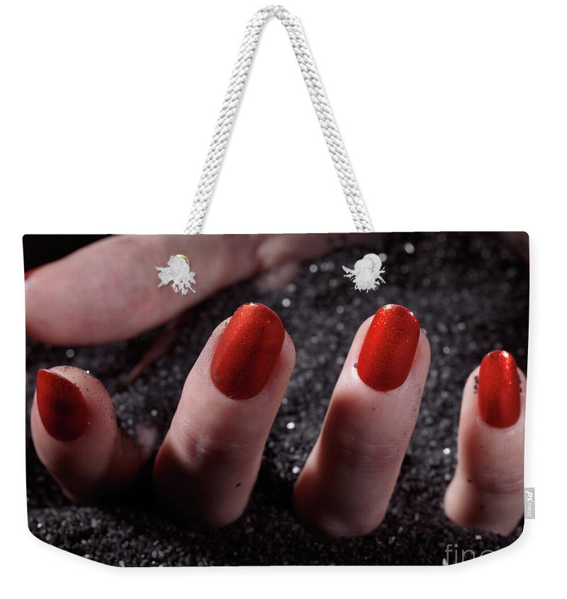 Manicure Weekender Tote Bag featuring the photograph Woman Hand With Red Nail Polish Buried In Black Sand by Oleksiy Maksymenko