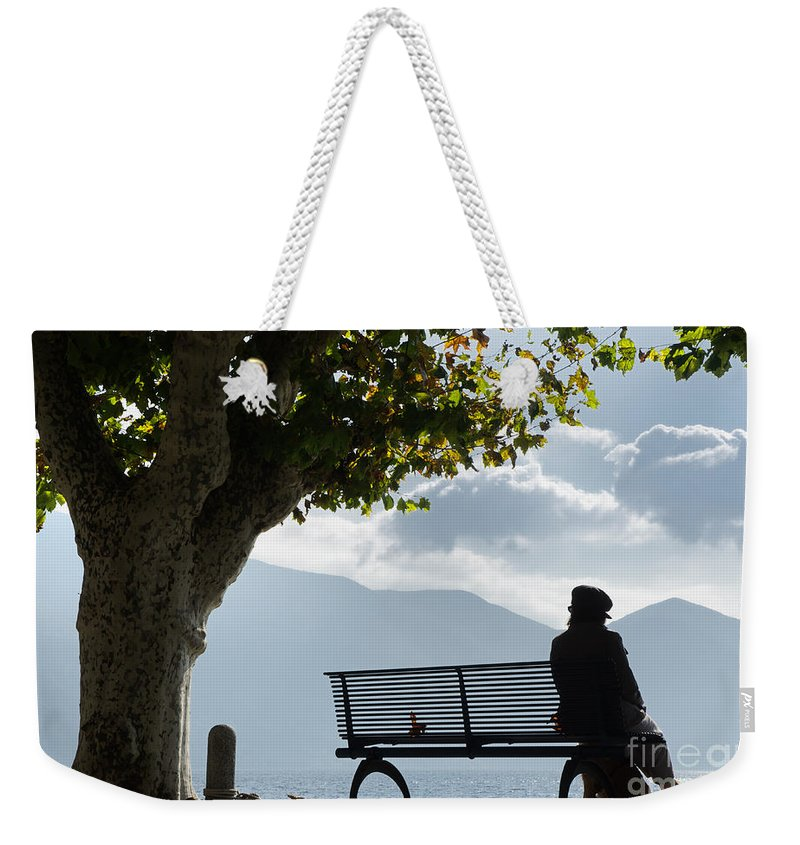 Woman Weekender Tote Bag featuring the photograph Woman Sitting On A Bench by Mats Silvan