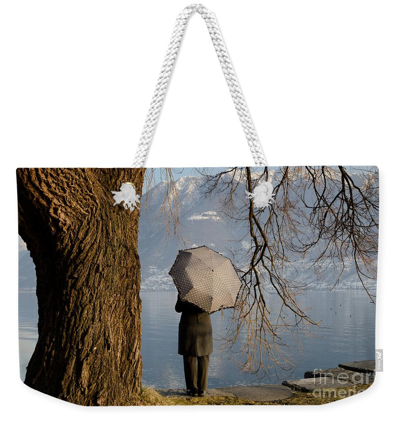 Woman Weekender Tote Bag featuring the photograph Woman With An Umbrella by Mats Silvan