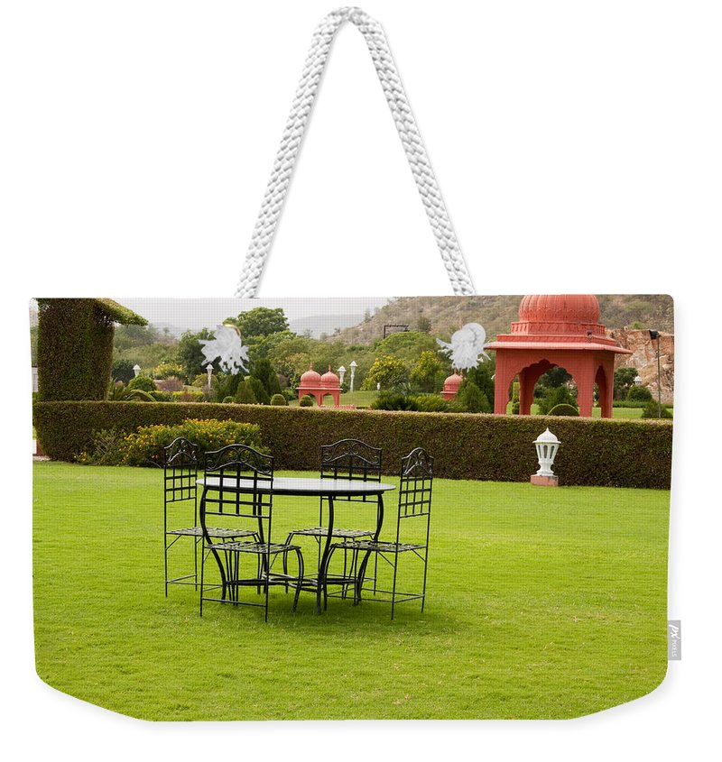 India Weekender Tote Bag featuring the photograph Wrought Metal Chairs Around A Table In A Lawn by Ashish Agarwal