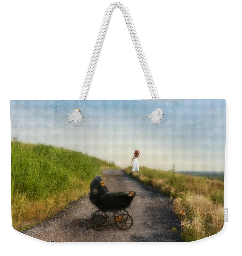 Woman Weekender Tote Bag featuring the photograph Young Woman And Baby Buggy On Dirt Road by Jill Battaglia