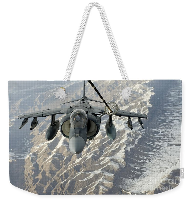 Military Weekender Tote Bag featuring the photograph An Av-8b Harrier Receives Fuel by Stocktrek Images