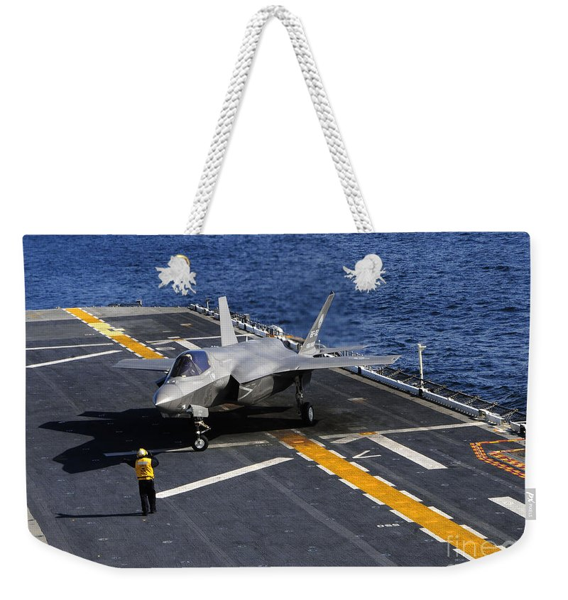 Stealth Weekender Tote Bag featuring the photograph An F-35b Lightning II Makes A Vertical by Stocktrek Images