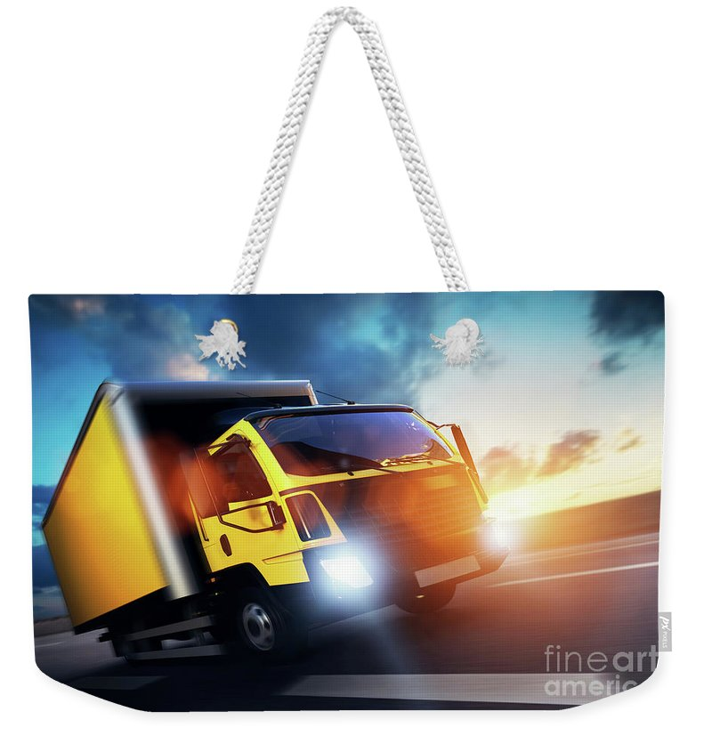 Truck Weekender Tote Bag featuring the photograph Commercial Cargo Delivery Truck With Trailer Driving On Highway At Sunset. by Michal Bednarek