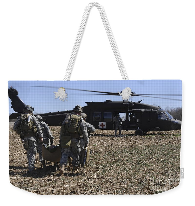 Us Army Weekender Tote Bag featuring the photograph Green Berets Move A Simulated Casualty by Stocktrek Images