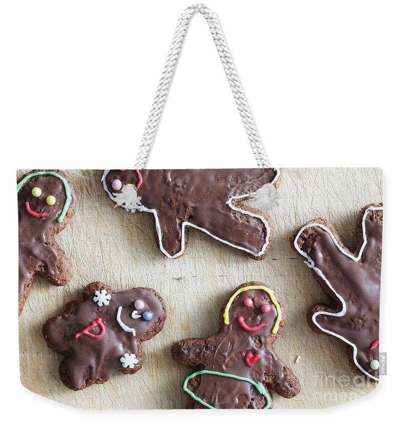 Gingerbread Weekender Tote Bag featuring the photograph Handmade Decorated Gingerbread People Lying On Wooden Table by Michal Bednarek