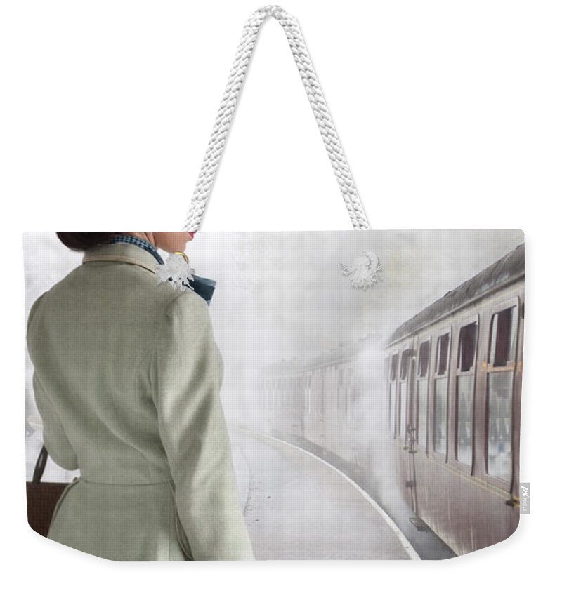 Woman Weekender Tote Bag featuring the photograph 1940's Woman On A Railway Platform With Steam Train by Lee Avison