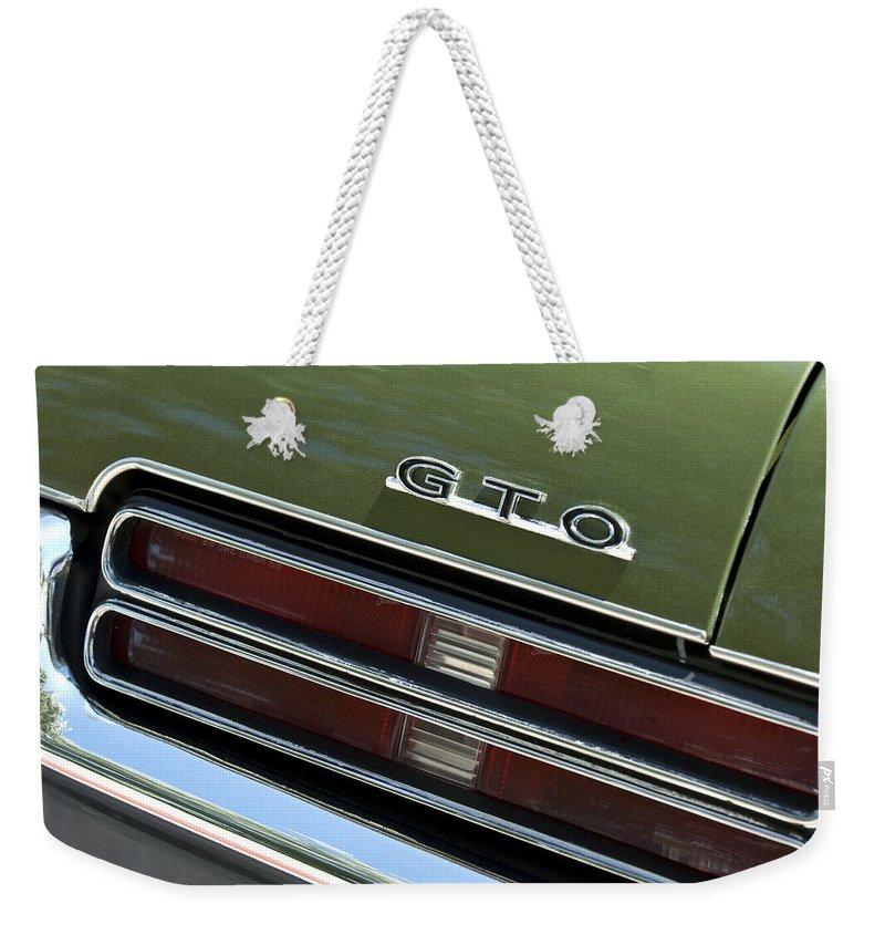 1969 Pontiac Gto Emblem Weekender Tote Bag featuring the photograph 1969 Pontiac Gto Taillight Emblem by Jill Reger