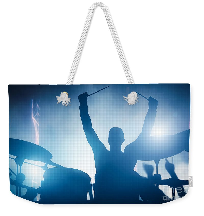Drums Weekender Tote Bag featuring the photograph Drummer playing on drums on music concert. Club lights by Michal Bednarek