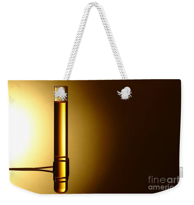 Brass Weekender Tote Bag featuring the photograph Laboratory Test Tube In Science Research Lab by Olivier Le Queinec