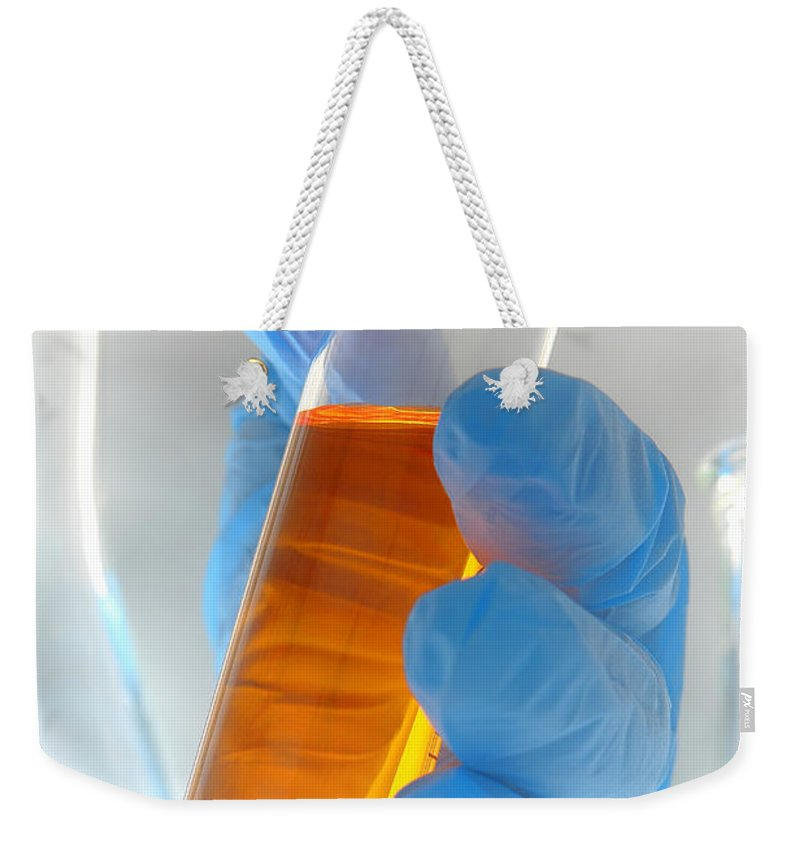 Cylinder Weekender Tote Bag featuring the photograph Scientific Experiment In Science Research Lab by Olivier Le Queinec