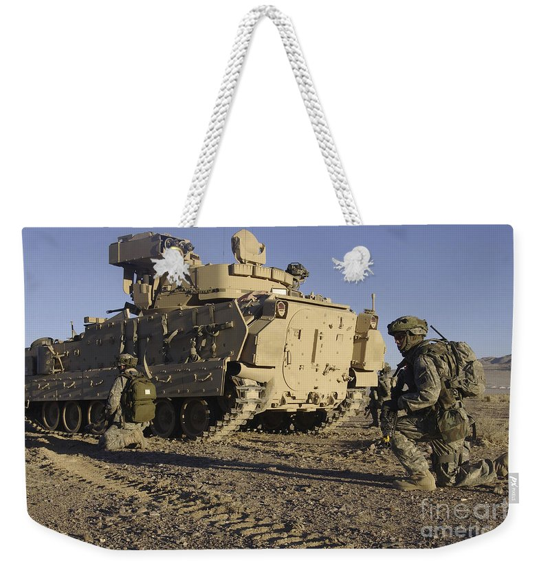 Army Weekender Tote Bag featuring the photograph U.s. Army Soldiers Provide Security by Stocktrek Images