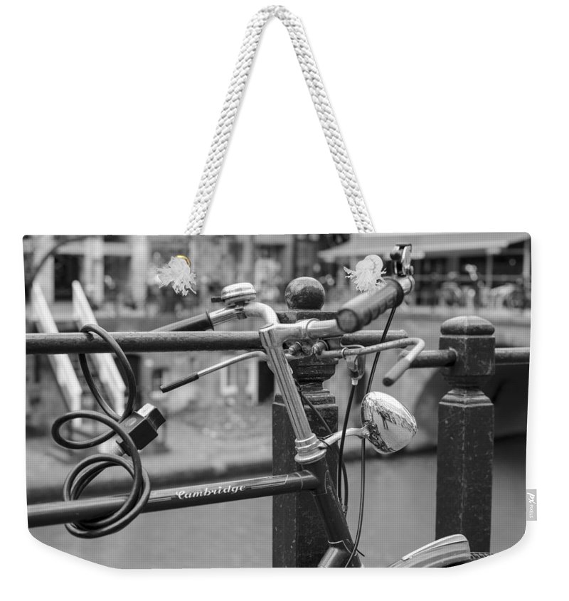Bicycles Parked At Fence On Street Weekender Tote Bag featuring the photograph A Bicycle Parked At Fence, Netherlands by David Ortega Baglietto