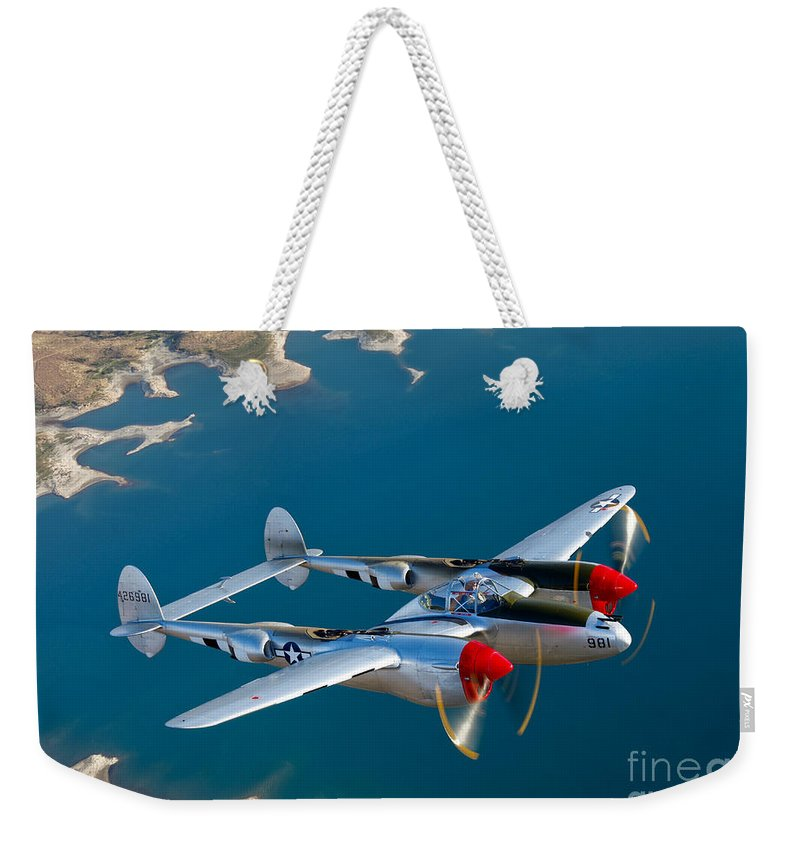 World War Ii Weekender Tote Bag featuring the photograph A Lockheed P-38 Lightning Fighter by Scott Germain