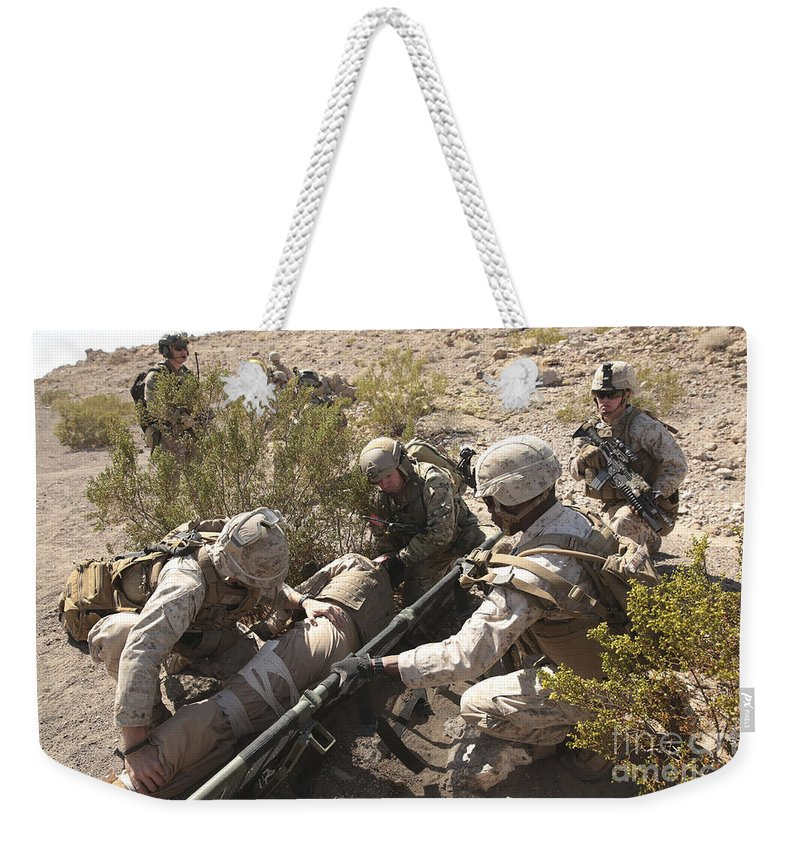 Combat Weekender Tote Bag featuring the photograph A Medic Treats Injuries On A Downed by Stocktrek Images