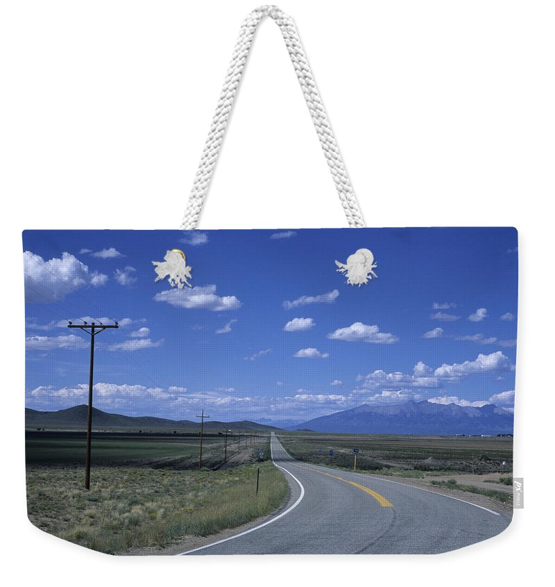 Colorado Weekender Tote Bag featuring the photograph A Road Disappears Into The Distance by Taylor S. Kennedy