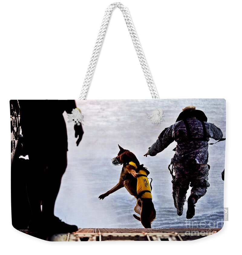 Military Weekender Tote Bag featuring the photograph A U.s. Soldier And His Military Working by Stocktrek Images