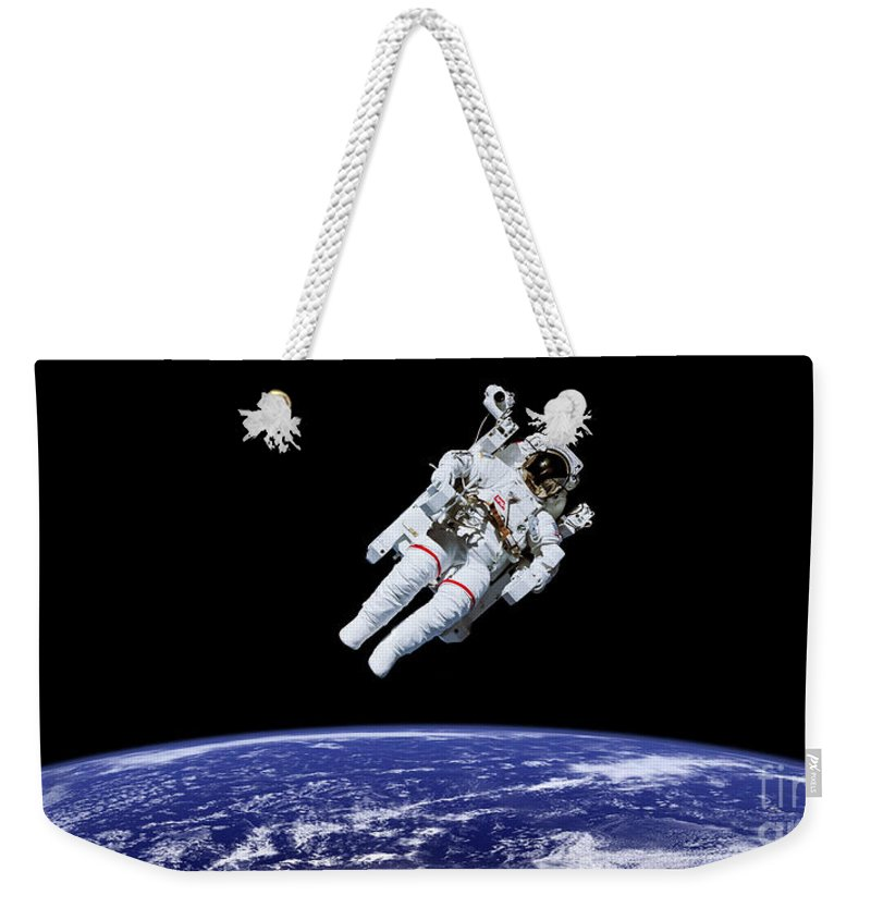Astronaut Weekender Tote Bag featuring the photograph Above Earth by Courtesy of NASA
