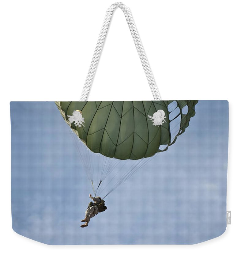 Airman Weekender Tote Bag featuring the photograph An Airman Descends Through The Sky by Stocktrek Images