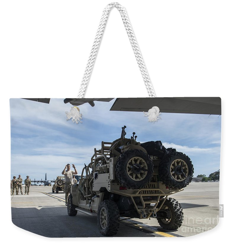 Exercise Emerald Warrior Weekender Tote Bag featuring the photograph An All-terrain Vehicle Is Guided Onto by Stocktrek Images