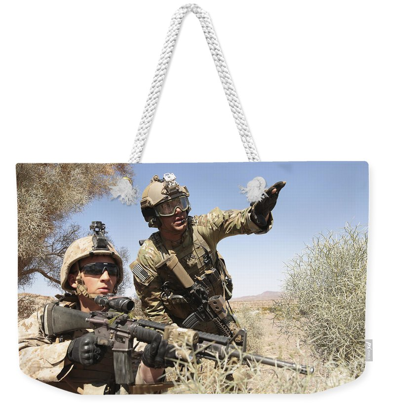 Combat Weekender Tote Bag featuring the photograph An Army Soldier Informs A Marine by Stocktrek Images