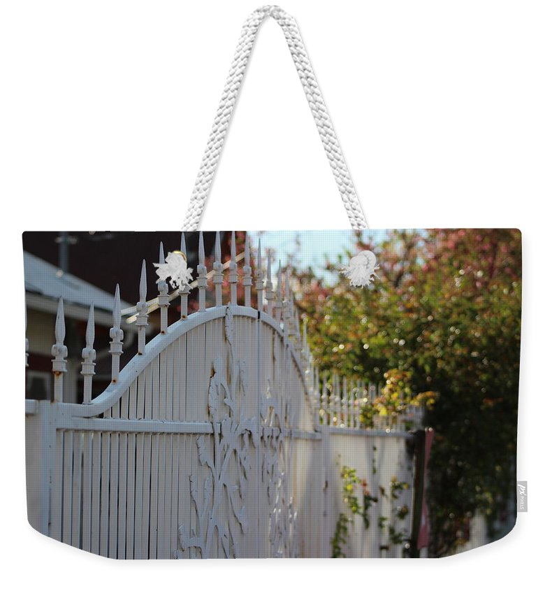 White Weekender Tote Bag featuring the photograph Angled Closeup Of White Washed Iron Gate To Garden by Colleen Cornelius