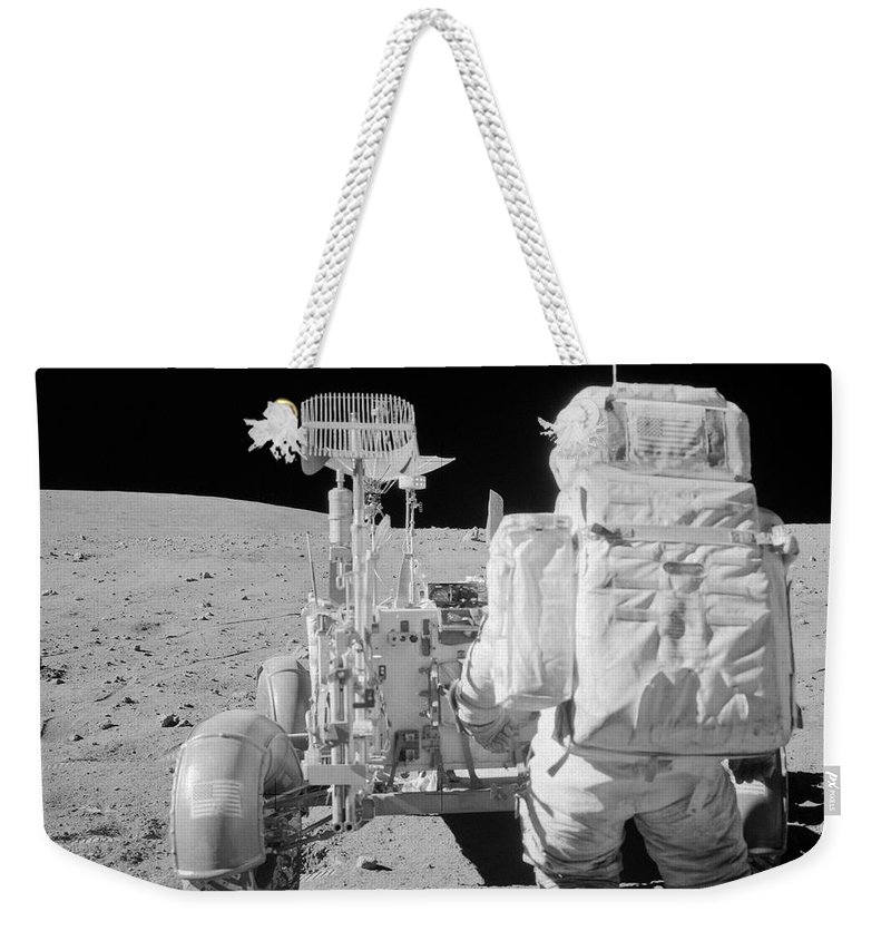 1972 Weekender Tote Bag featuring the photograph Apollo 16 Astronaut Reaches For Tools by Stocktrek Images